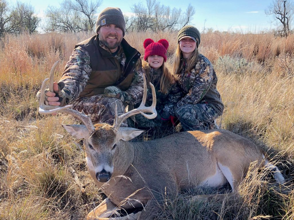 Brad Jones and his daughters with a buck that Brad has recently hunted.