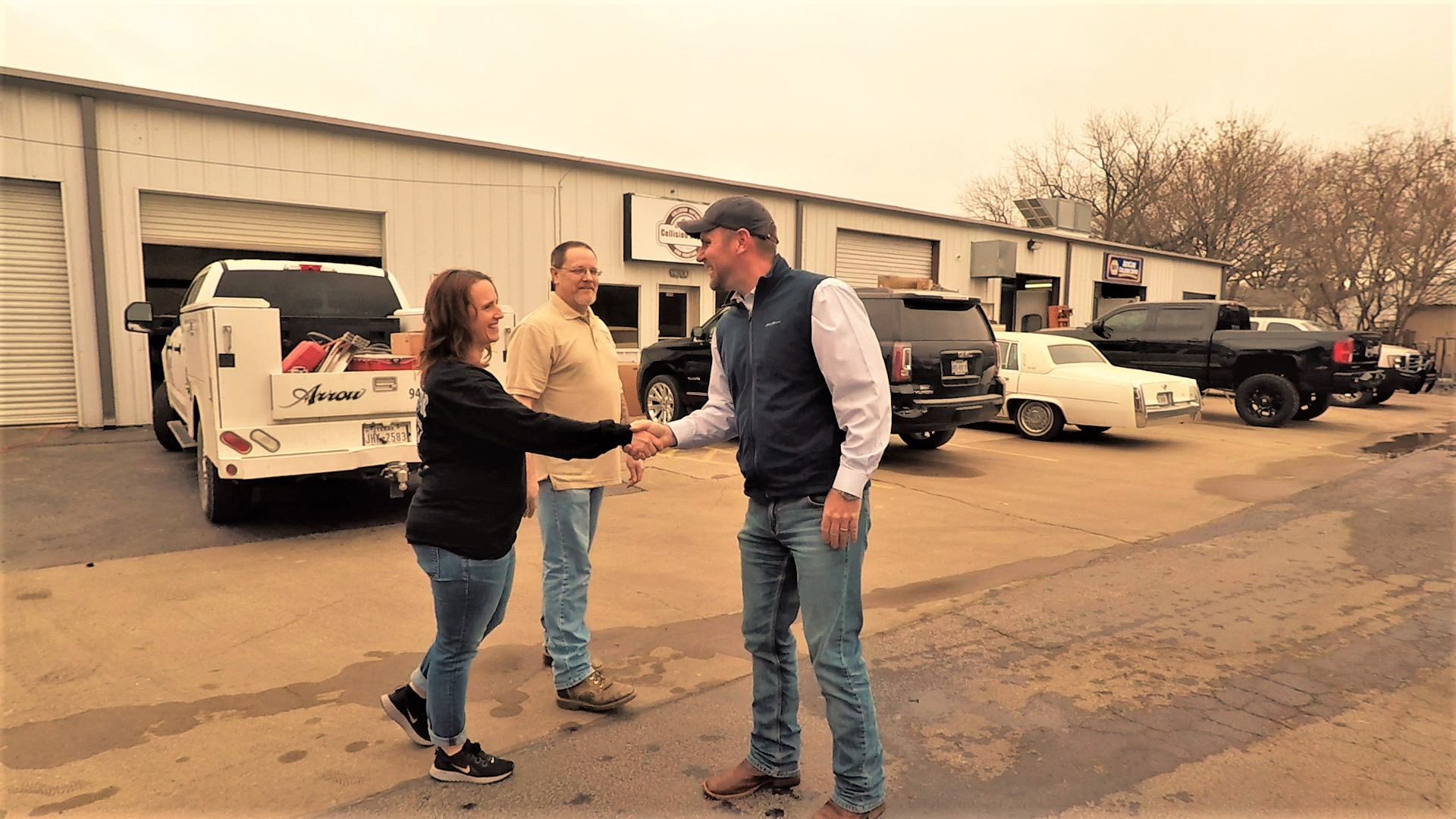 Brad Jones of Trophy Insurance shaking hands with some of his business insurance customers at Lee Collision in Mineral Wells, Texas.