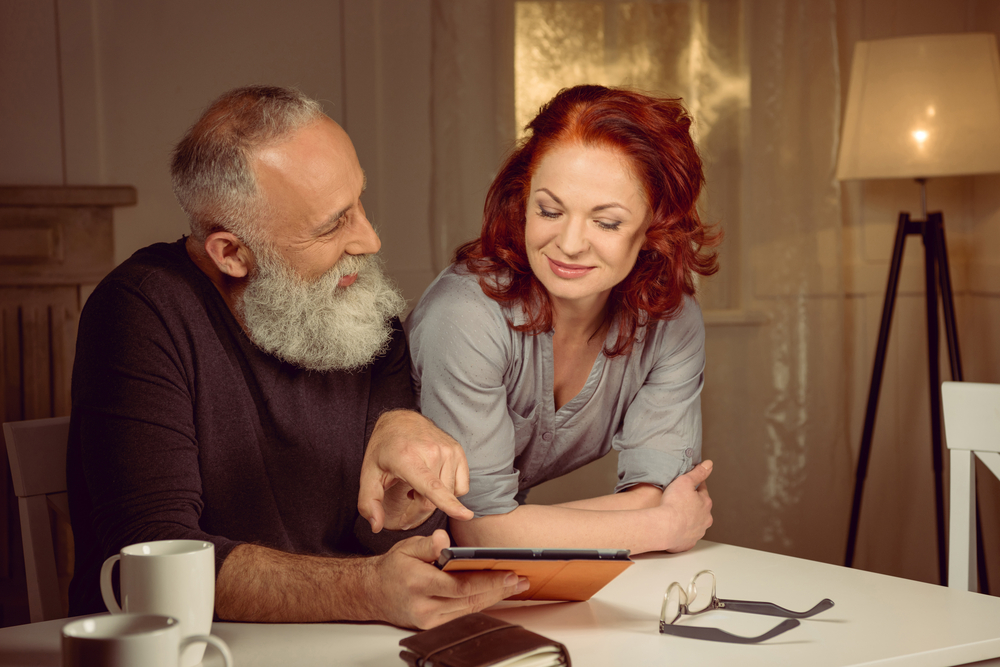An older couple look at their great insurance policy online.