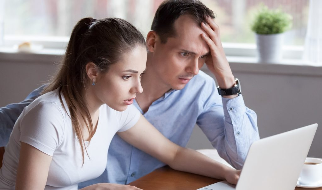 Upset millennial couple disappointed losing money in online lottery, worried man and woman look at laptop screen reading bad news, husband and wife get negative email from bank or eviction notice
